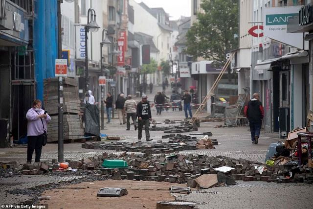 People walk past rubble in a street devastated by the floods in Euskirchen, western Germany
