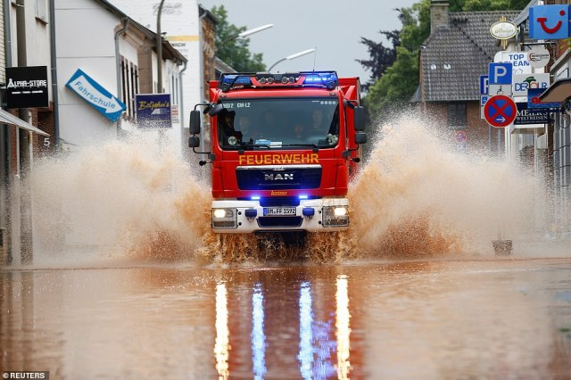 A fire truck drives through a flooded street following heavy rainfalls in Erftstadt, Germany