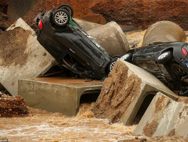 Cars lie crumpled against concrete blocks that once formed part of the sewer system after the ground gave way due to a landslide in Blessem, Germany