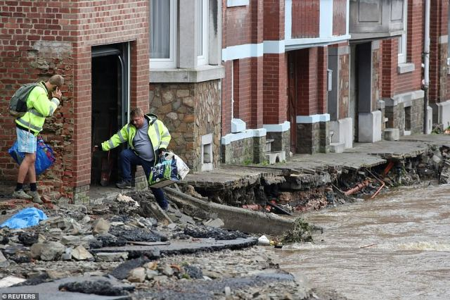 People stand next to a partially flooded street, following heavy rainfalls, in Trooz, Belgium