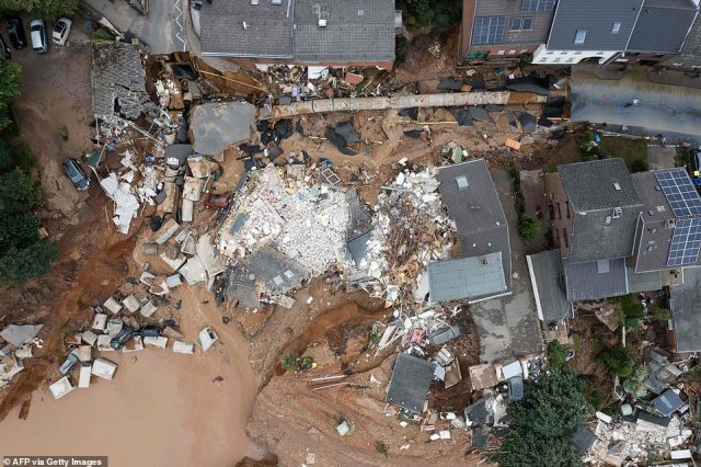 An aerial view of the landslide shows how what used to be a street corner collapsed into the ground, taking the road, houses, cars and other debris with it