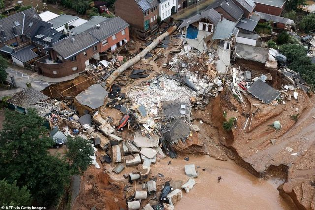 Chunks of road, pieces of concrete sewage pipe, cars, and wrecked buildings are shown collapsed into a watery hole on the outskirts of Blessem, Germany, following the landslide