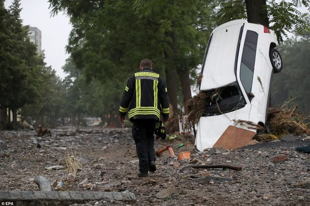 A fireman walks past the ruins of a car inBad Neuenahr-Ahrweiler, Germany, after it was swept away by floodwaters