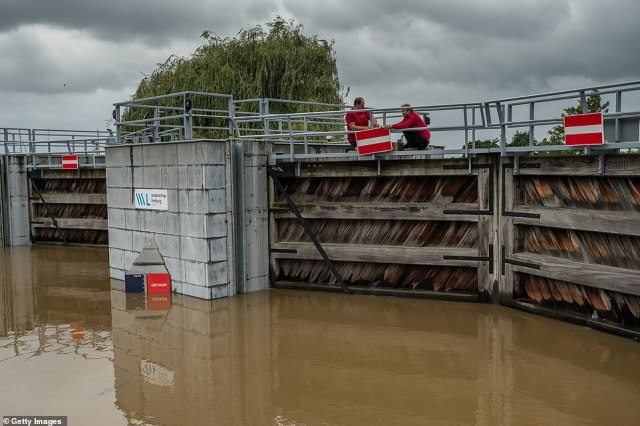 Workers attach a no entry sign on a closed waterway to protect the city of Roermond, Netherlands, following flooding