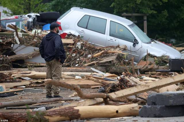 A person stands amid the debris near a damaged car after flooding in Bad Neuenahr-Ahrweiler, Germany