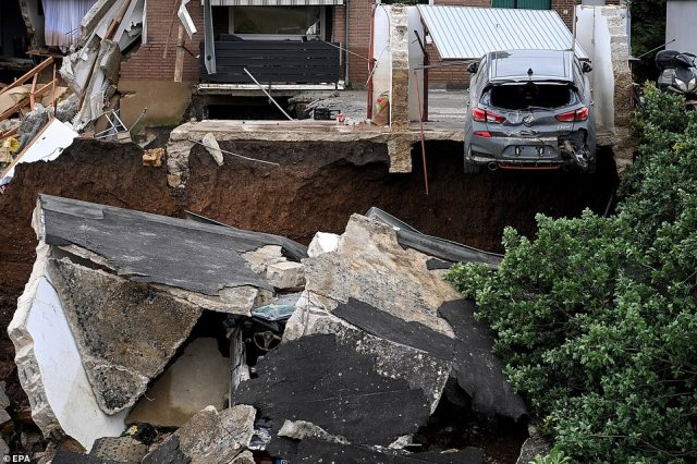 A partly-destroyed car that was parked in a garage is left hanging off the edge of a cliff after the ground collapsed in Blessem