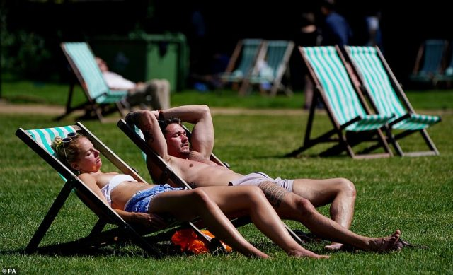 Sunbathers lounge on deck chairs at Green Park in London this afternoon