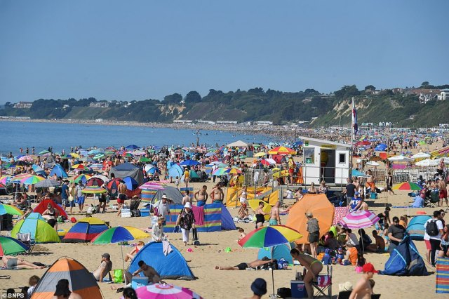 On Branksome beach in Poole, Dorset, crowds of sun-seekers sat on the hot sand and enjoyed the sea air