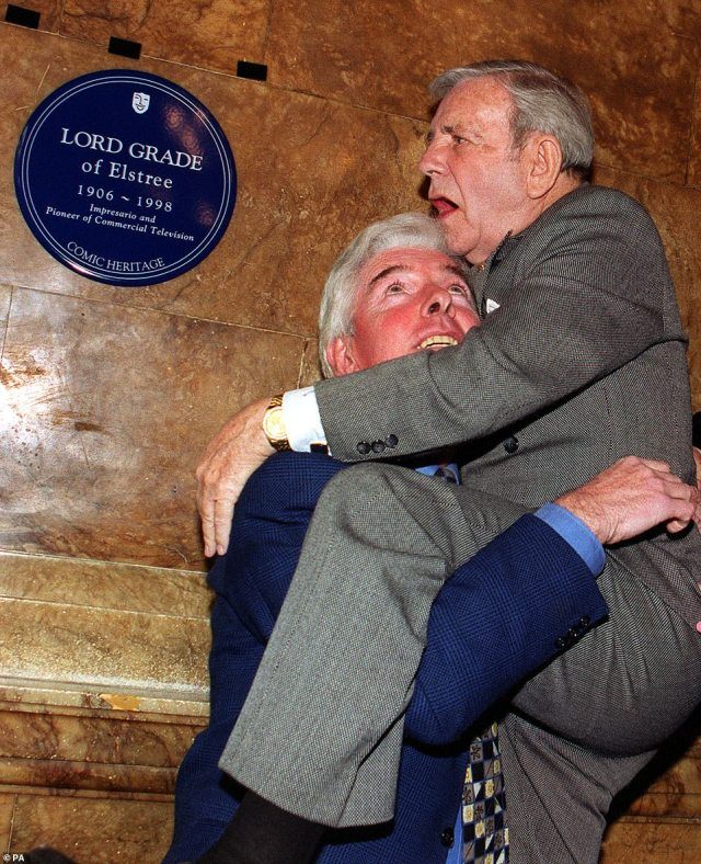 Sir Norman Wisdom uses fellow comedian Tom O'Connor to get a better view of a blue plaque unveiled in honour of Lord Grade at the London Palladium, March 19, 2000