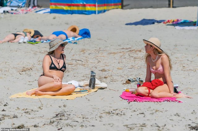 Two women enjoy the sunny weather on the beach in West Wittering, West Sussex