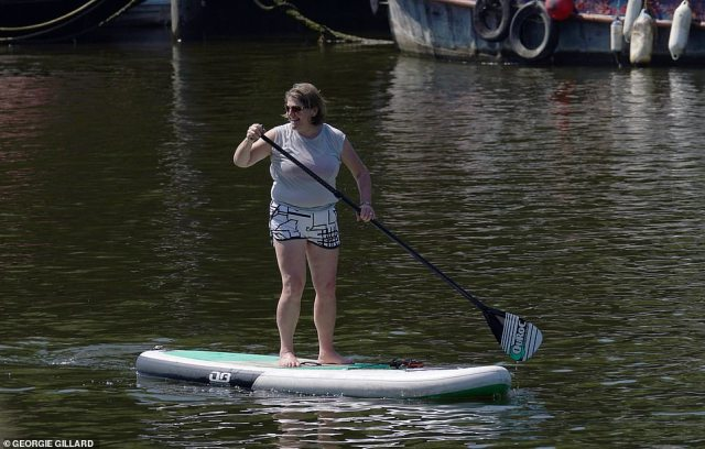 A paddle boarder enjoys the sun as she rides up the River Thames in Richmond