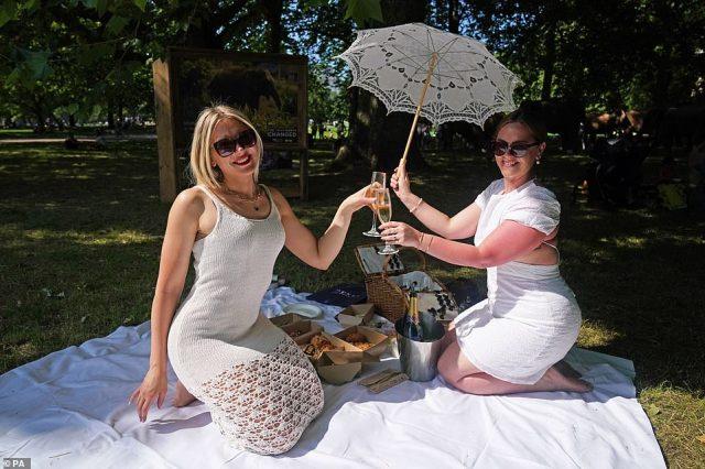 Kirstina Katkute (left) and Alexandra Barton enjoy the hot weather in Green Park, London