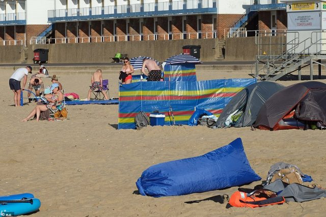 On Branksome beach people bask in the summer heatwave, with the balmy weather due to last until so-called 'Freedom Day' on Monday
