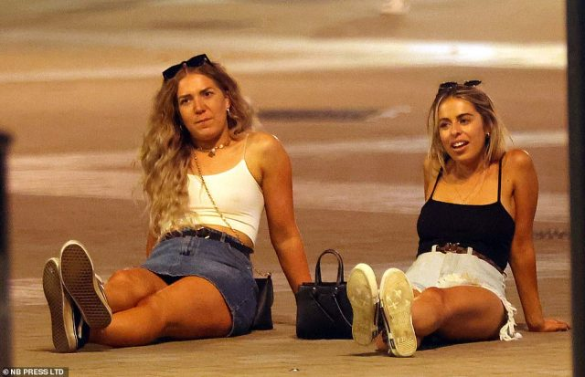 People sit on the street as the enjoy a night out in Leeds last night following a week of heavy rain and thunderstorms across the UK