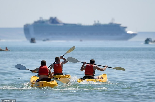 Kayakers take to the cool waters on a beach in Weymouth as scores of people across the country enjoy the heatwave today