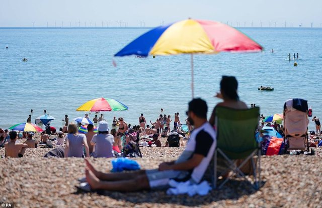 People enjoy the hot weather on Brighton beach in East Sussex today as temperatures across the country soar