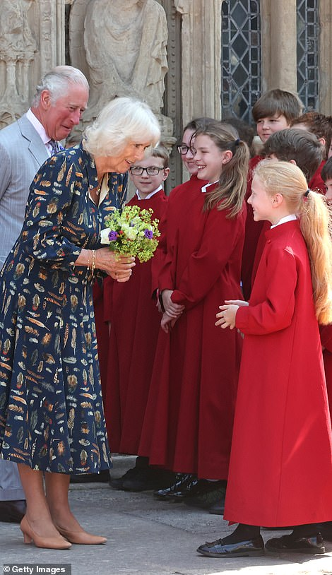 TheDuchess of Cornwall is presented with a bunch of posys by the youngest member of the Cathedral's choir on her departure from Exeter Cathedral
