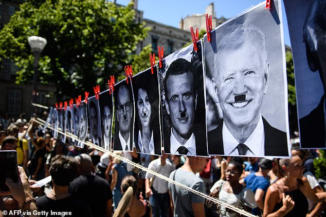 Pictures of world leaders bearing Adolf Hitler moustaches are seen in Paris, where protesters described a 'health dictatorship'