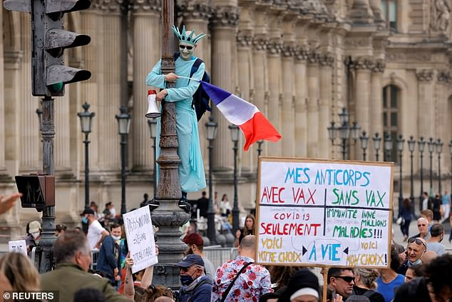 A protester dressed as the Statue of Liberty waves a flag during a demonstration in Paris on Saturday as another holds a sign emphasising that it should be an individual's choice whether or not to get vaccinated