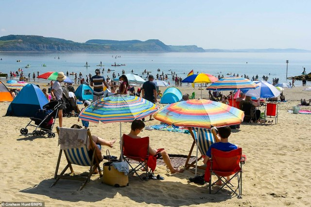 Sunbathers and visitors flock to the beach to enjoy the scorching hot morning sunshine at the seaside resort of Lyme Regis in Dorset