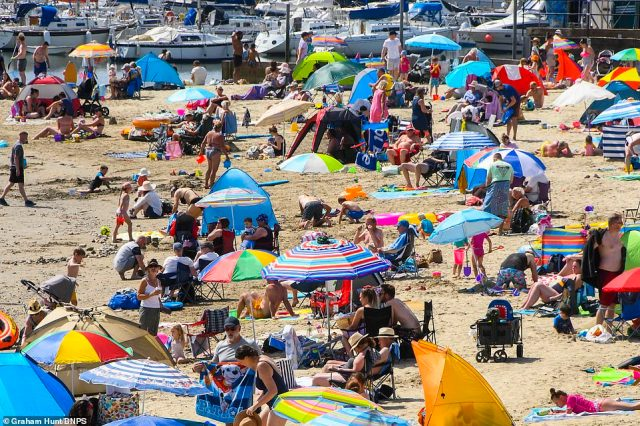 Hordes of sunworshippers have taken to the beach in Lyme Regis to soak up the scorching sunshine in Dorset