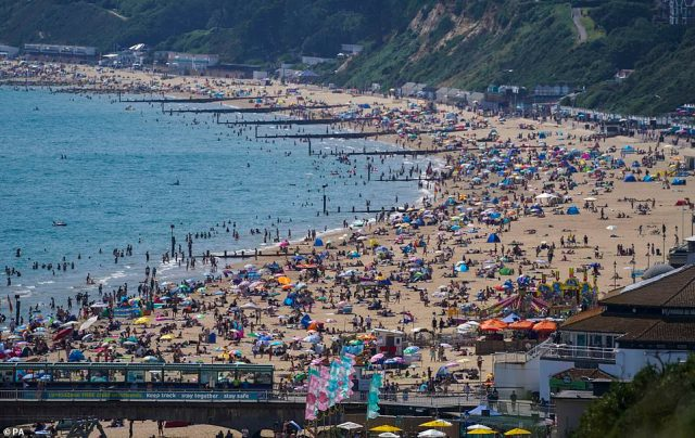 Hordes of people flock to the beach in Bournemouth to soak up the scorching hot sun on Monday