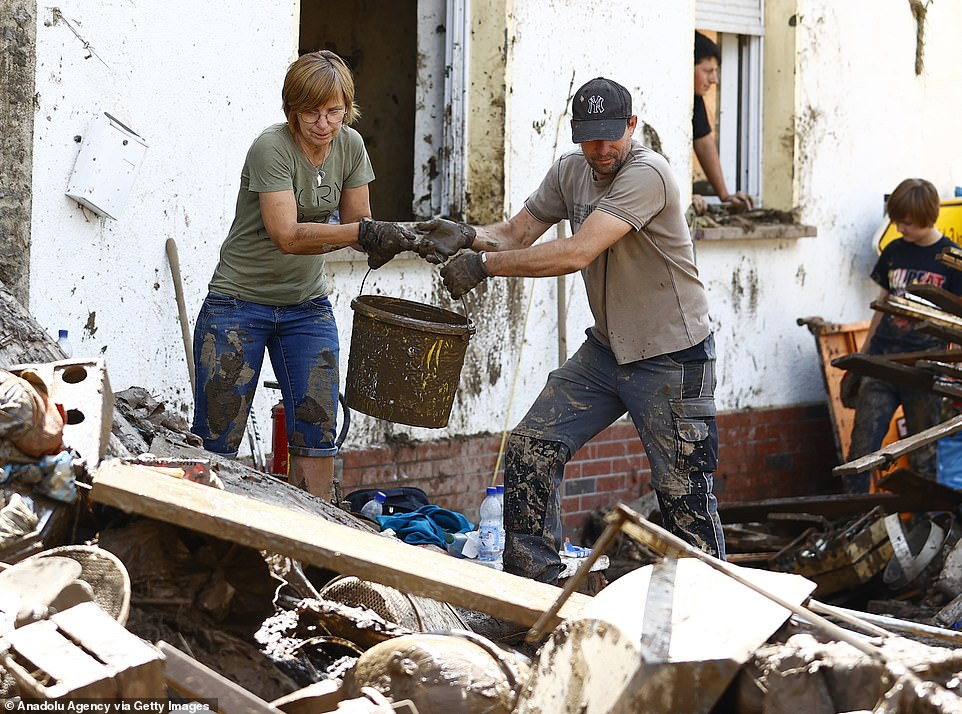 Two people help clear toxic mud out of a home inSchuld, western Germany, following devastating floods that hit last week