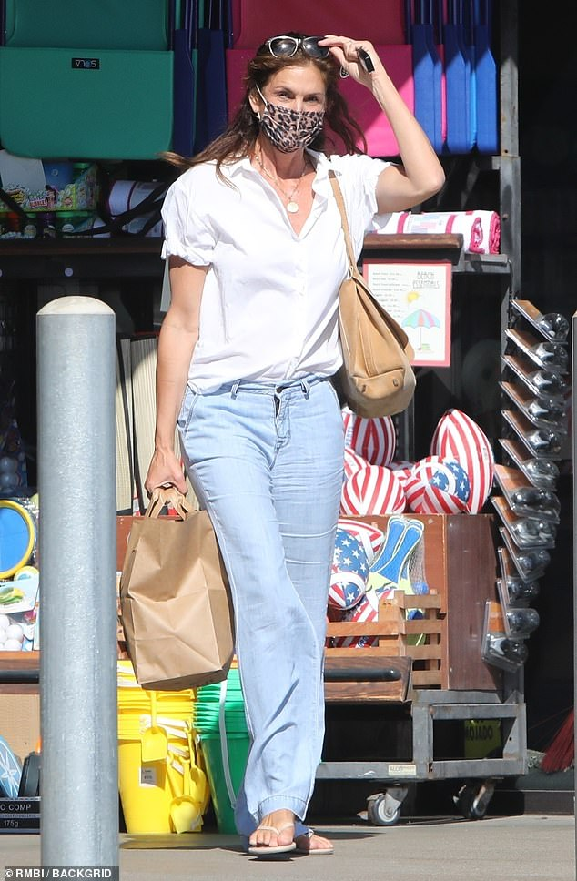 Covered up: Cindy Crawford made sure to obey the rules as she went shopping in Malibu on Monday wearing an animal print mask in keeping with a new COVID-19 mandate in LA County
