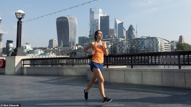A jogger runs along the Thames near London's Tower Bridge this morning, with the recent heatwave set to continue throughout the week