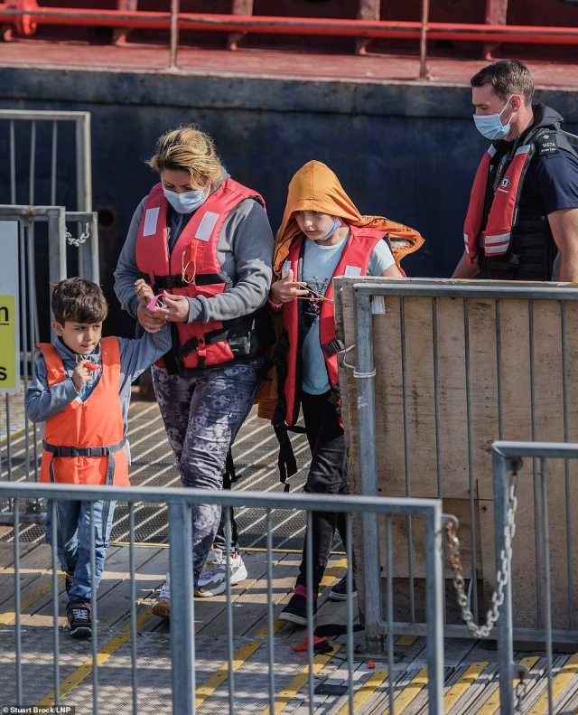 A migrant family is escorted by a Border Force officer as they are brought ashore at Dover Harbour in Kent