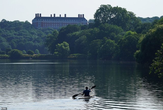 A kayaker travels along the River Thames near Ham Common, London on another sweltering morning in the English capital