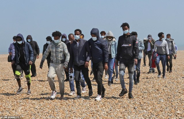 Migrants are seen walking up the beach at Dungeness in Kent after they were intercepted by the coastguard