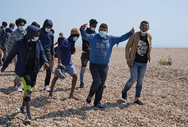 A group of people thought to be migrants are escorted from the beach in Dungeness, Kent, by Border Force officers following a small boat incident in the Channel