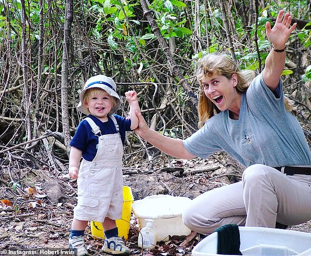 Cute!In the sweet photograph, a baby Robert is seen smiling while his mother gripped onto him with her arms up in the air