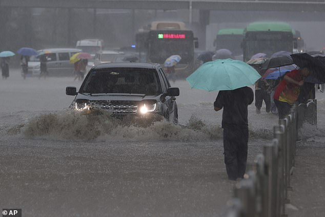 A Range Rover ploughs through floodwaters covering a road in the Chinese city ofZhengzhou, after it was inundated with seven months' of rain in a single day