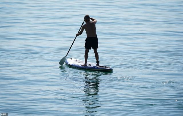 A man is pictured paddle boarding in the sea just off of Bournemouth Beach, Dorset as hundreds of people enjoyed the summer sun on Tuesday