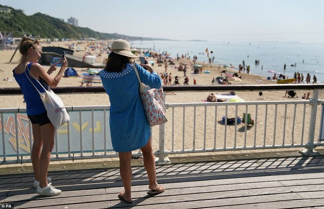 Two women take snaps of the sea before they join the hundreds of people who have converged on Bournemouth Beach on Tuesday, July 20