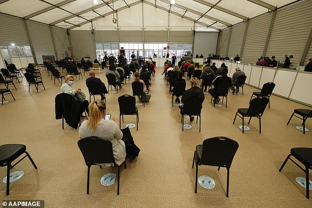 Victorians sit waiting to be called in for their vaccination at a mass coronavirus vaccination hub at the Showgrounds in Melbourne