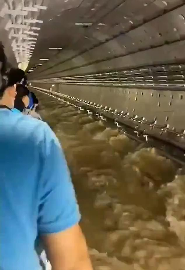 Passengers from one of the stranded trains were led to safety along the trackside as flood torrents gushed past their feet