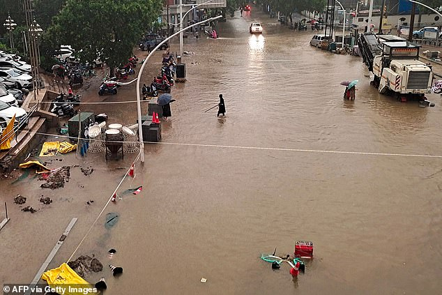 Construction equipment stands idle after a building site in downtownZhengzhou was inundated with water on Wednesday
