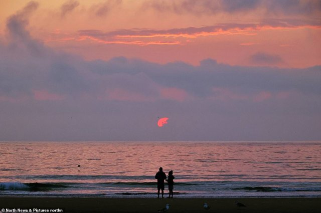 A couple take in the sunrise at Tynemouth Longsands beach in North Tyneisde at the start of another hot day this morning