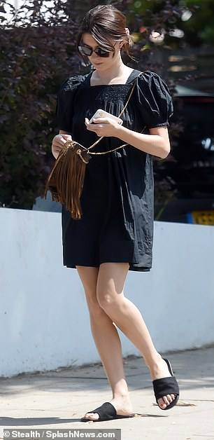 Keeping cool: Sporting a brown, fringed cross-body bag, the Islington-born star teamed the outfit with a comfortable pair of black sandals