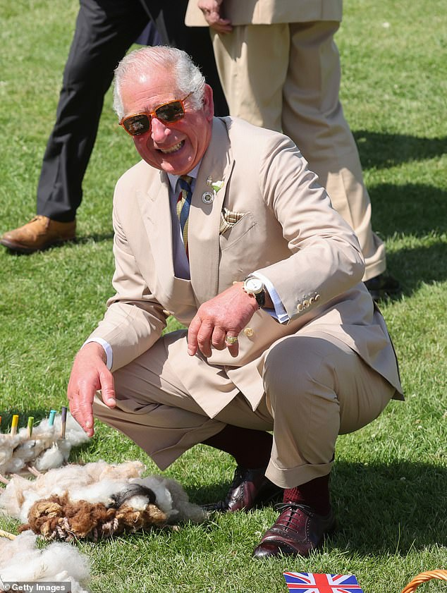 Prince Charles beams as he crouches down to speak with young people in the nearby Victoria Park