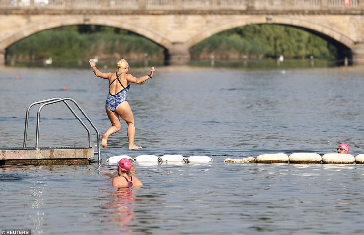 A woman jumps into the Serpentine lake at Hyde Park in the warm early morning sunshine in London today