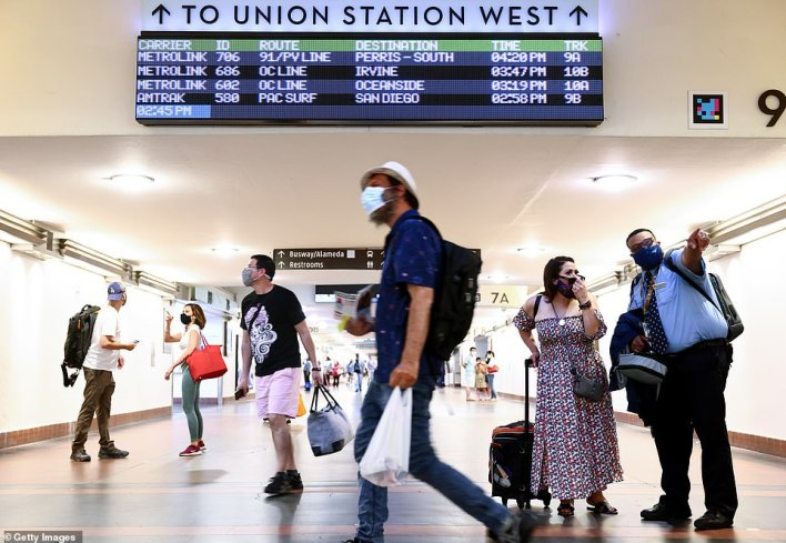 At least 17 counties in California - making up more than half of the state's residents - are urging residents to wear masks indoors amid the spread of the Indian 'Delta' variant. Pictured: People wear face coverings as they pass through Union Station in Los Angeles, California, July 2021