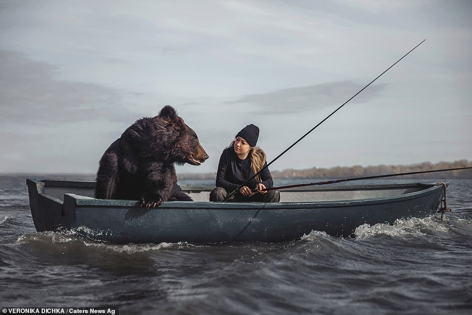Pictured: Archie, a rescued brown bear, together with his ownerVeronika Dichka fishing on a boat inNovosibirsk in Russia