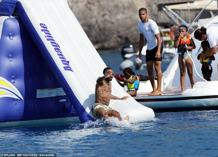 Daddy takes the lead: Raheem was seen throwing himself down a waterslide as he encouraged his children to follow suit