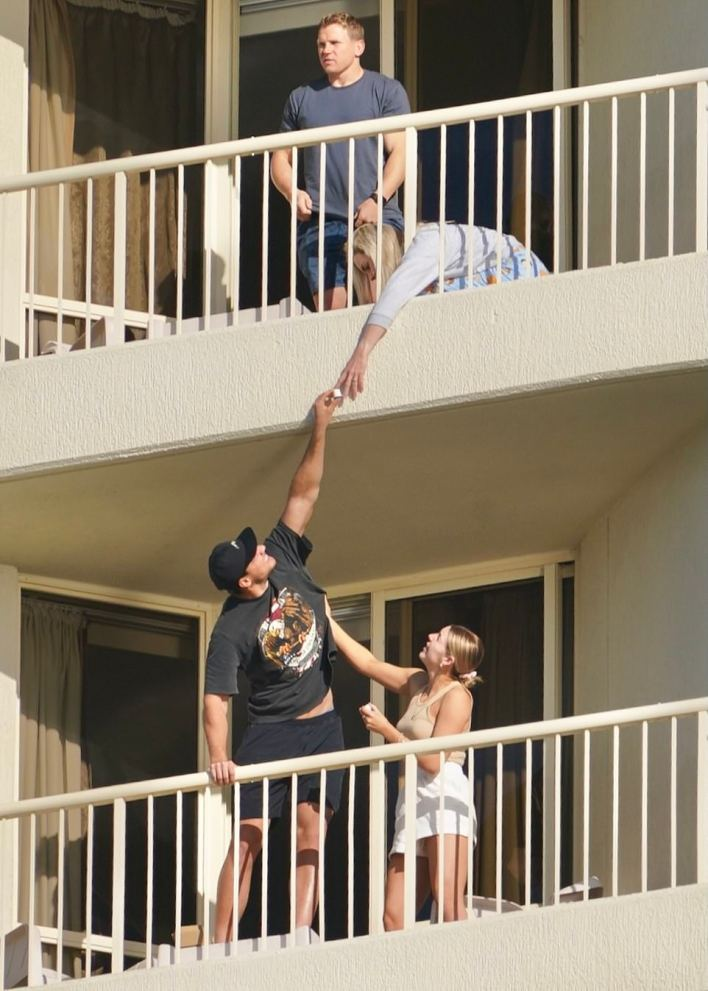 Pictures on Thursday show men and women staying inside the Novotel hotel in Surfers Paradise as a part of the NRL's bubble passing lollies to the rooms either side of them as well as to people on floors above and below.
