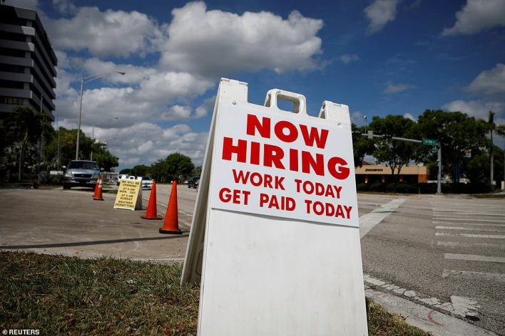 A 'Now Hiring' sign advertising jobs at a hand wash is seen along a street in Miami, Florida in 2020