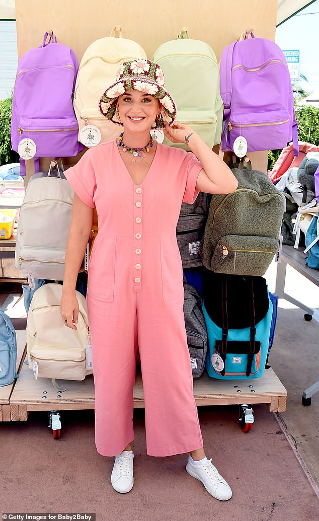 Summer style: Perry, 36, kept cool on the hot LA day in a short-sleeved pink jumpsuit with buttons down the front and added a pair of comfy white sneakers and a colorful collar